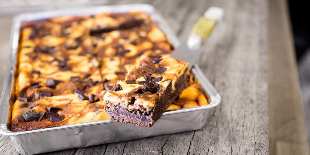 Cakesmiths espresso cheesecake brownie traybake with slice removed on a wooden background.