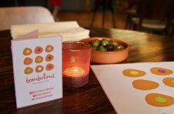 Bomboloni - Bristol restaurant launch. Bomboloni logo and social handles card. Olives and a candle.