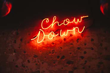 Chow down neon sign at hubbox restaurant launch Bristol