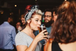 Woman enjoying a drink at the Hubbox Bristol launch.